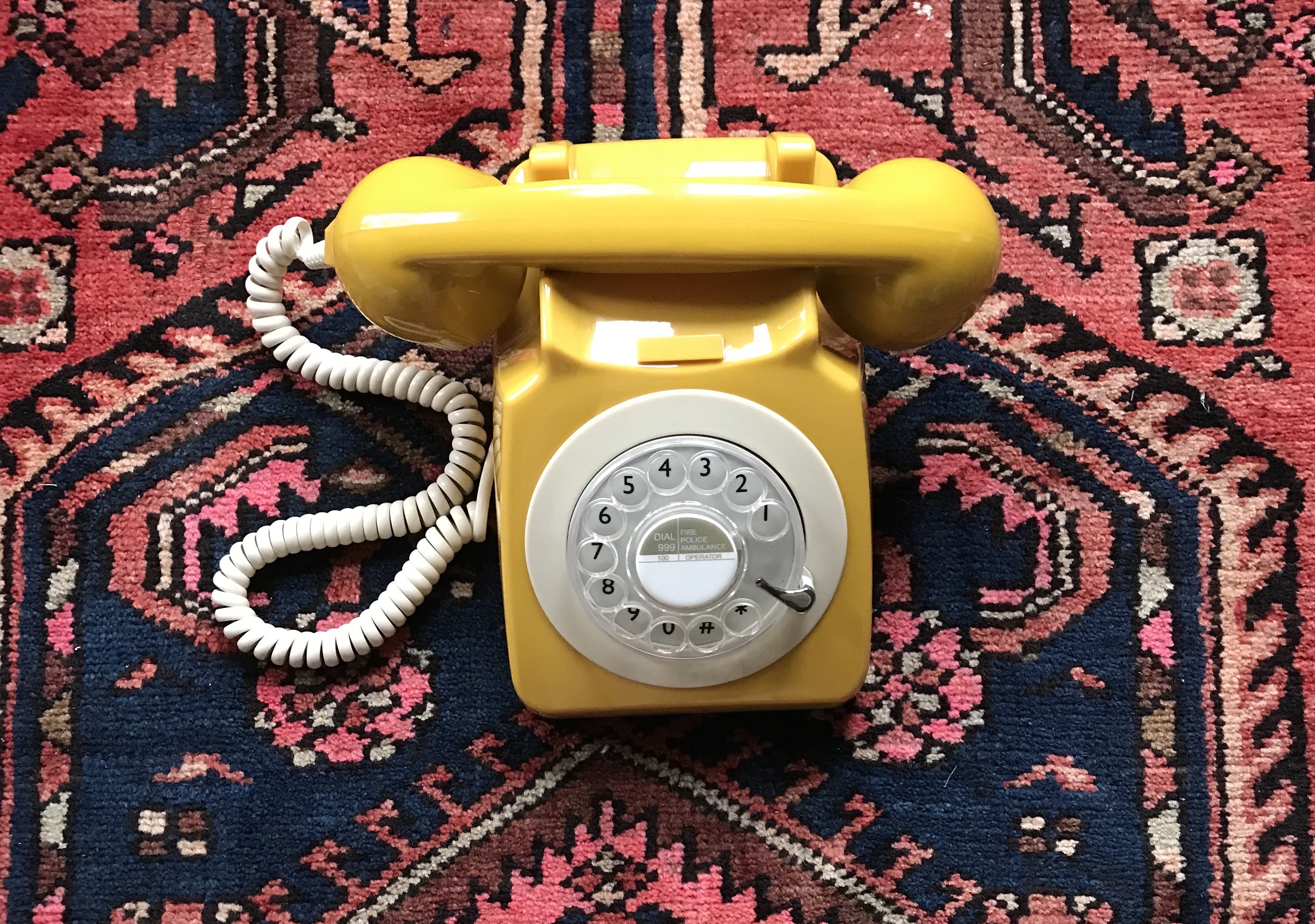 Old-school yellow rotary phone on carpet.