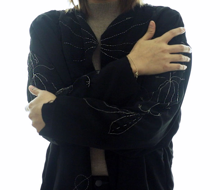 Person wearing embroidered jacket, hugging themselves.