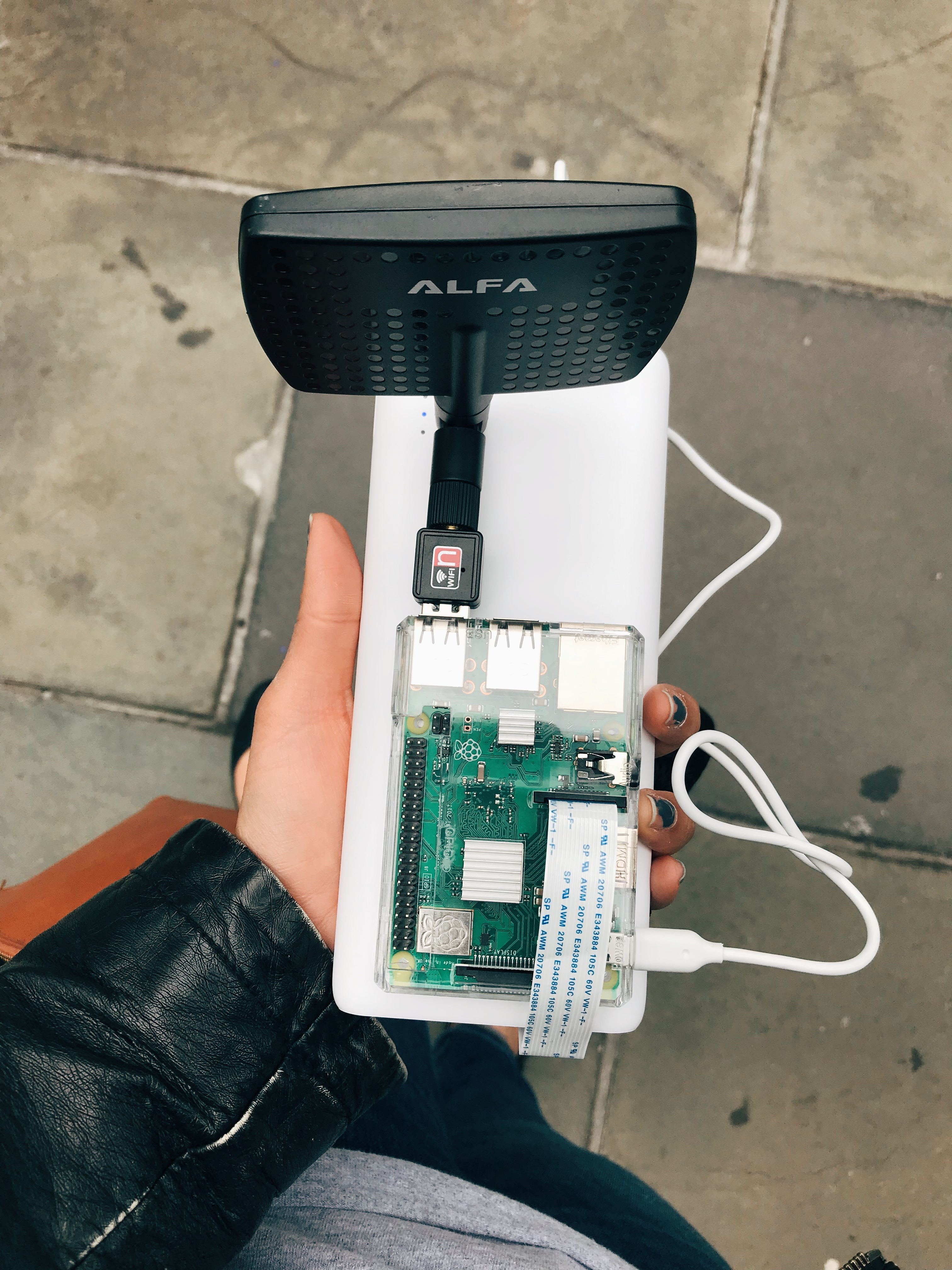 A hand holding a portable battery device and a raspberry pi with WiFi antenna attached.